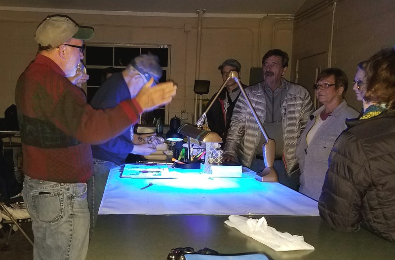 Clair Mellinger educates Rockingham Bird Club members while Charles Ziegenfus evaluates an owl under UV light