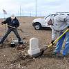 Justin Kent,left, and Jeff Kissinger,  Broomfield Parks, dig out the 2 grave markers for Shep the Turnpike Dog during the move of Shep's grave from the intersection of Hwy. US 36 and Hwy. 121 to the Depot Hill Museum on Wednesday.<br /> October 14, 2009<br /> Staff photo/David R. Jennings