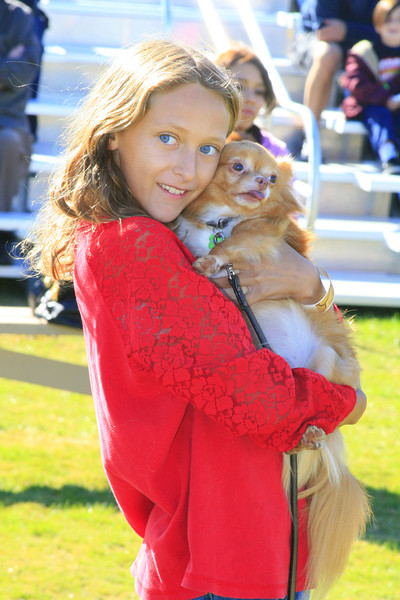 Paige Owens, 11, cuddles with Stewie during the dog-owner look alike contest at Strut Your Mutt.
