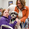 Kathy Briscoe greets Cindy Staveley and therapy dog Gronk, from TheraPAWS, at the Arc of Opportunity in Fitchburg on Wednesday afternoon. SENTINEL & ENTERPRISE / Ashley Green