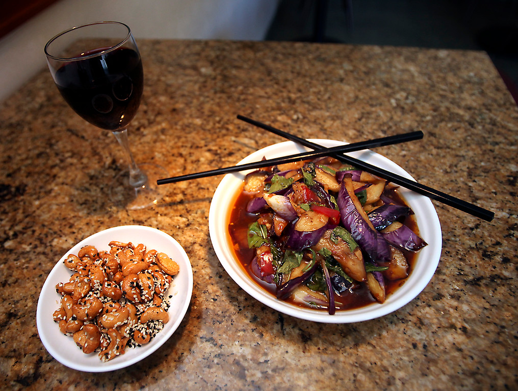 . O\'Mei\'s Taiwan egg plant with basil, and sesame candied cashews, served with a glass of red wine. (James Clark/Sentinel)