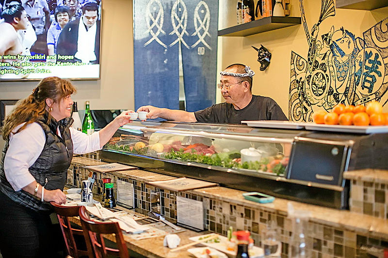 . Owner Masao Nakagawa accepts a gift of sake from a customer at his new restaurant Naka Sushi in Capitola. (Carolyn Kelley - Santa Cruz Sentinel)