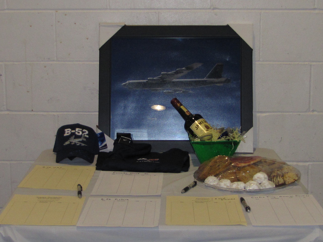 The favorite things table included a B-52 hat and picture, bottle of Jameson with shot glasses, plate of cookies, many golf certificates, a Harley Davidson gift certificate and a Corvette golf shirt.