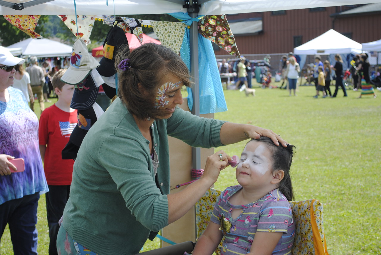 Erin Peterson prepared to turn Amiya Waldvogel into a kitty with face paint during the Annie and Mary Day in Blue Lake on Sunday.  (Hunter Cresswell - The Times-Standard)