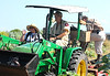 "<div align=""left"">Tim Wilkinson (on the back of the tractor), Warden Chester Smith's son-in-law, puts on his snake guards before leaving with Chester (driving the tractor).  I'm (Marcy Spears, volunteer) waving at Peggy Wilkinson, who was taking the photo.  <em>Photo Credit: May 2009, Peggy Wilkinson.</em></div>"