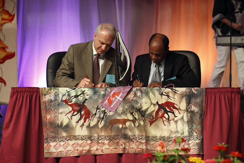 Bishops Thomas Bickerton, left, and Eben Nhitiwa sign the Zimbabwe Partnership agreement between Zimbabwe and Western PA conferences. A soapstone sculpture on the table before them was a gift from Zimbabwe to Bishop Bickerton.