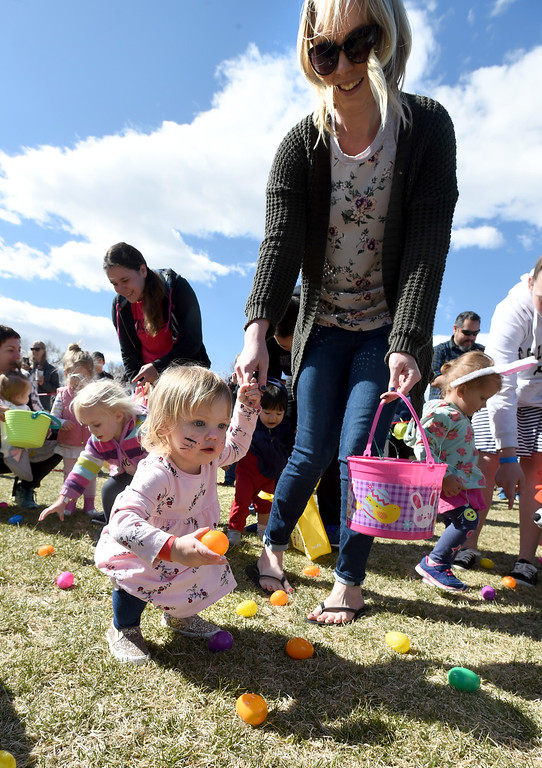 . Sawyer Bliven, 20-months, gets help from mom, Kayla, during the 8th Annual White Fields Community Church Easter Egg Hunt at Roosevelt Park in Longmont on Saturday. Cliff Grassmick  Photographer  March 31, 2018