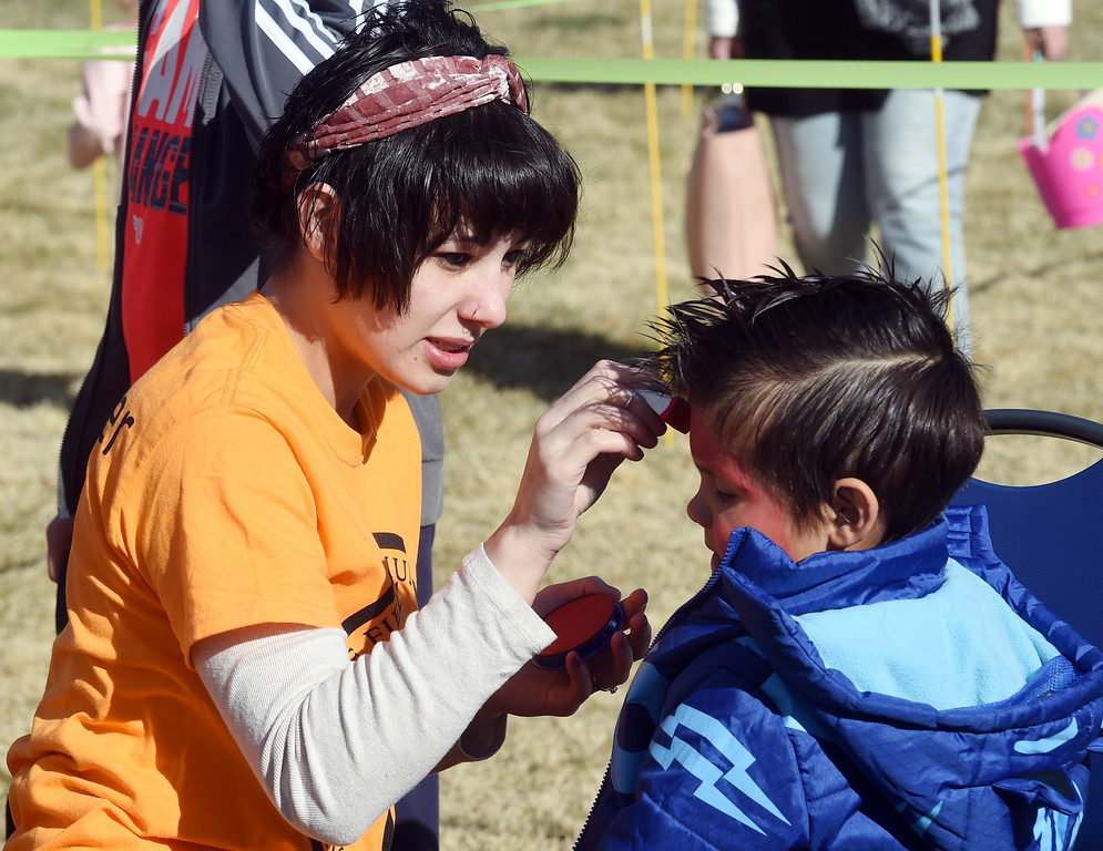 . Keilah Hansen, paints Spiderman on the face of London Regalado during the 8th Annual White Fields Community Church Easter Egg Hunt at Roosevelt Park in Longmont on Saturday. Cliff Grassmick  Photographer  March 31, 2018