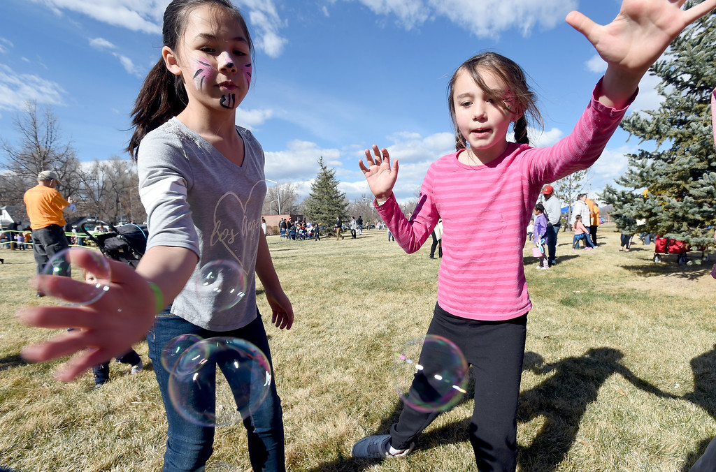 . Aaliyah Bustamante, left, and Autumn Seifford, swats at bubbles during the 8th Annual White Fields Community Church Easter Egg Hunt at Roosevelt Park in Longmont on Saturday. Cliff Grassmick  Photographer  March 31, 2018