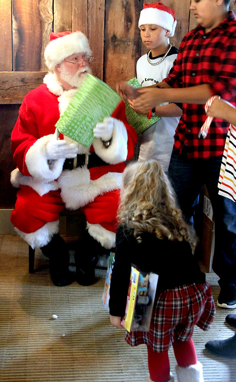 . Santa, played by Mike Gowing, hands out gifts to kids from area shelters, with help from Santa\'s elfs, Simon Rabbitt, 12, and Sachh Luthra, 12 at the annual holiday party held at Gibbet Hill in Groton. SUN/David H. Brow