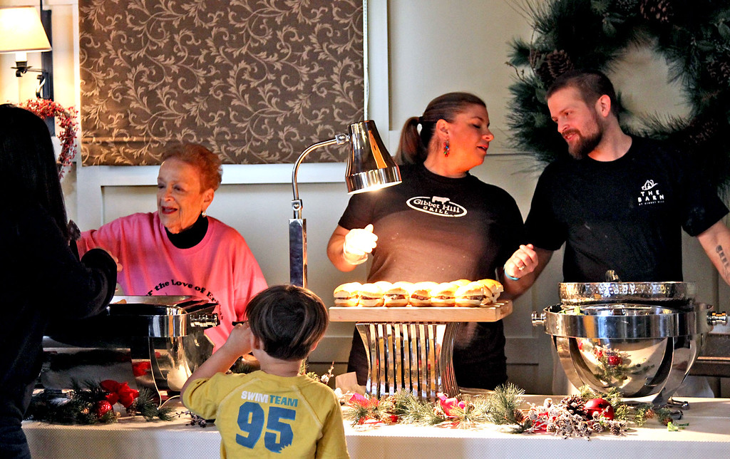 . Helping out on the food line for the annual holiday party for homeless from area shelters, is L-R, Elaine Goodman volunteer, and Gibbet Hill staff Kristen Donahue and  Chef Keith Goguen. SUN/David H. Brow