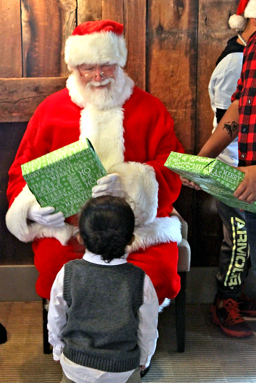 . Santa, aka: Mike Gowing of Acton, hands out gifts to homeless kids form area shelters at the annual holiday party at Gibbet Hill in Groton. SUN/David H. Brow