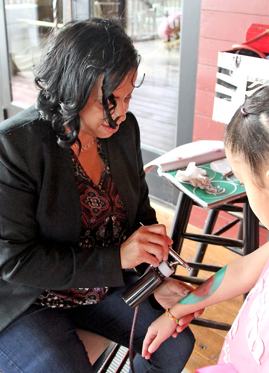 ". Regina Miranda of ""Scribble Dibble\"", puts a airbrush tattoo on a girl at the annual holiday party for area shelters, held at Gibbet Hill in Groton. SUN/David H. Brow"