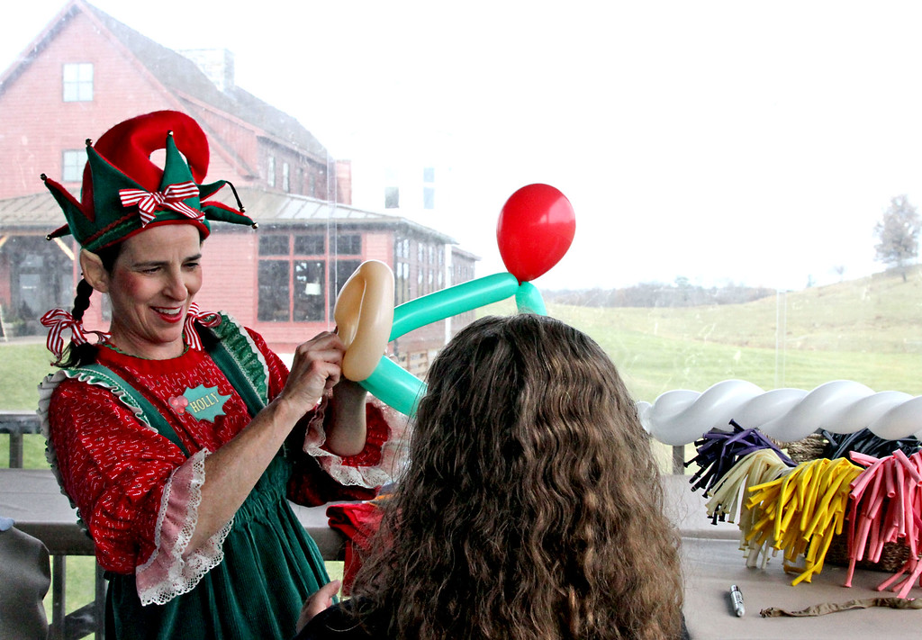 ". Making a holiday balloon hat for a ypoung girl from an area shelter is ""Holly The Elf\"" aka: Nicole Portwood, at Gibbet Hill in Groton. SUN/David H. Brow"