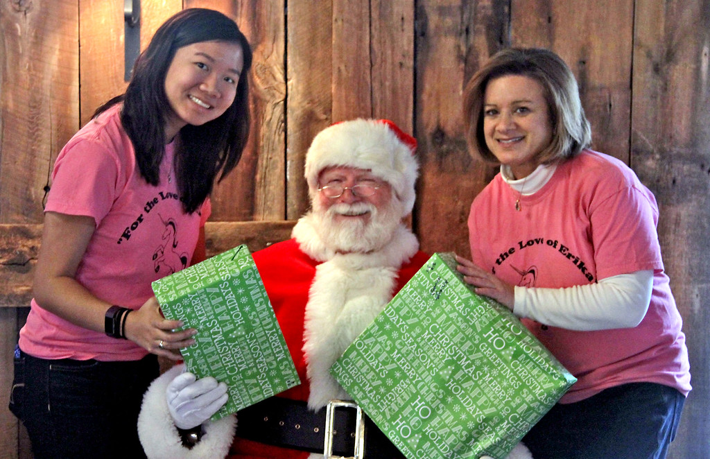 . Handing out gifts for the homeless kids from area shelters is L-R, Taylor Goodman-Leong, 19, Santa played by Mike Gowing, and Laura Goodman, at  annual holiday party held at Gibbet Hill in Groton. SUN/David H. Brow