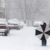 Another storm hit the north central region on Tuesday less then a week after the last storm that dropped 18+ inches on the region. Raul Rosando uses his umbrella to keep the wind off of him so he could smoke as he made his way through the storm in Fitchburg. SENTINEL & ENTERPRISE/JOHN LOVE