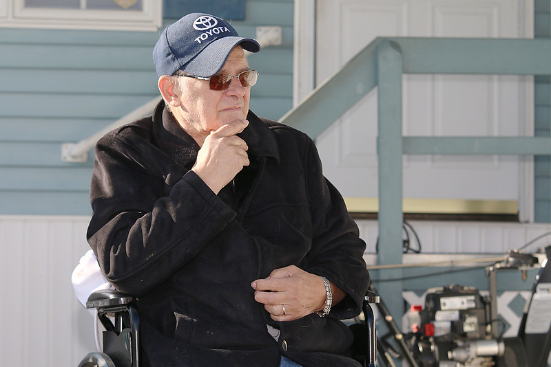 Navy Veteran Seaman Donald Denoncourt, 77, watches as the 20 or so firefighters clean up the wood from his driveway as they where told they could not build a handicap ramp for him at his home in the Meadowbrook Acres mobile home park on Central Street in Leominster.  SENTINEL & ENTERPRISE/JOHN LOVE