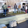 Firefighters clean up the wood from Navy Veteran Seaman Donald Denoncourt's, 77, driveway as they where told they could not build a handicap ramp for him at his home in the Meadowbrook Acres mobile home park on Central Street in Leominster.  SENTINEL & ENTERPRISE/JOHN LOVE