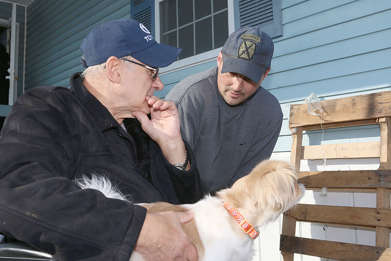 Navy Veteran Seaman Donald Denoncourt, 77, listens to Leominster Fire Lt. Ryan Young as he tells him that they will figure out how to get him in and out of his home at Meadowbrook Acres On Central Street. They had plans to build a Handicap ramp for him on Monday but as they started they were told due to regulations a the mobile home park they could not build what they had planned. In his lap is his dog Bella. SENTINEL & ENTERPRISE/JOHN LOVE