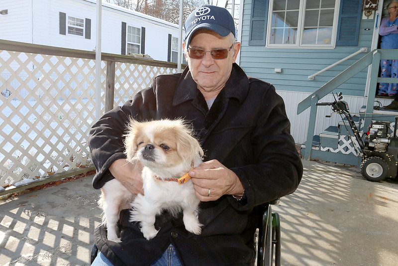 Navy Veteran Seaman Donald Denoncourt, 77, watches, with his dog Bella, as the 20 or so firefighters clean up the wood from his driveway as they where told they could not build a handicap ramp for him at his home in the Meadowbrook Acres mobile home park on Central Street in Leominster.  SENTINEL & ENTERPRISE/JOHN LOVE
