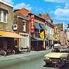 An0037 <br /> Hoofdstraat, gezien in noordelijke richting. Links (met oranje zonnescherm) boekhandel Wagner, dan het woonhuis van J. Verkleij (voorheen had hij hier een zuivelwinkel). Vervolgens de fotozaak van Turk en de winkel van Duynstee. Verderop is het postkantoor nog te zien. Rechts op de voorgrond staat een goudkleurige Ford. Foto: 1974.