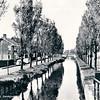 An0076 <br /> De Zandsloot stroomt van de Kagerplassen tot in de gemeente Voorhout. Er liggen enige platboomschuiten afgemeerd. Links langs de Postwijkkade staan meerdere auto's geparkeerd. Foto genomen vanaf de Oude Postbrug in westelijke richting. Foto: 1969