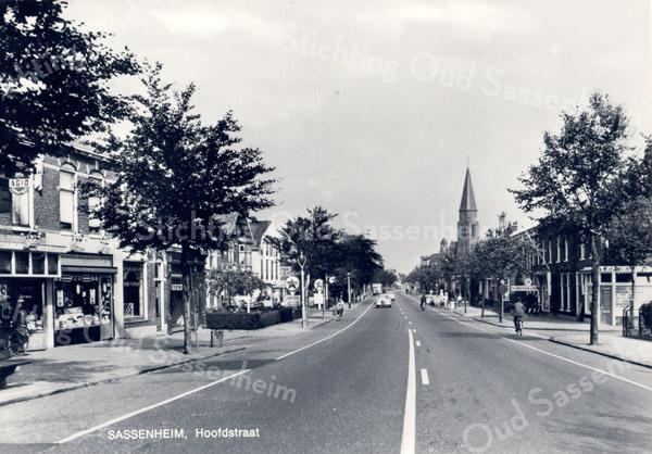 An0075 <br /> De Hoofdstraat, gezien vanaf de Oude Postbrug in noordelijke richting. Links kapper annex sigarenmagazijn Karremans. Daarnaast de inmiddels verdwenen kruidenier Eikelenboom en de zaak van Perfors. Rechts op de hoek van de Zuilhofstraat de groentezaak van W. van der Lans. Verderop zien we W. Moolenaar en de toren van de St. Pancratius. Foto: 1970.