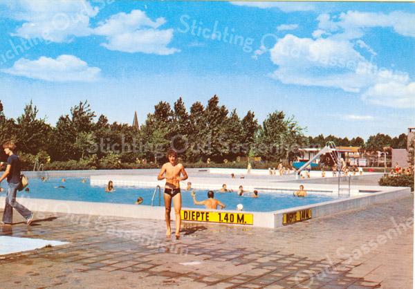 An0049 <br /> Zwembad Wasbeek, een open buitenbad, gebouwd in 1972. Op de achtergrond de toren van de St. Pancratius. Foto: 1974.