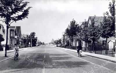 An0009<br /> De Hoofdstraat ter hoogte van de Concordiastraat kijkend in noordelijke richting. In de verte de H.H. Engelenbewaarderskerk in Lisse. Rechts het aannemersbedrijf van firma Dijkstra. Foto: begin jaren '60.