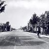 An0009<br /> Hoofdstraat ter hoogte van Concordiastraat kijkend in noordelijke richting. In de verte RK-kerk van HH Engelenbewaarders in Lisse. Rechts het aannemersbedrijf van firma Dijkstra. Links jongen op fiets, rechts man op bromfiets. Foto: begin jaren '60.