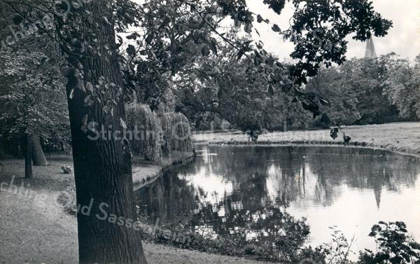 An0016<br /> Park met een deel van de vijver en gezicht op de RK-kerk St. Pancratius. Foto: begin jaren '60.