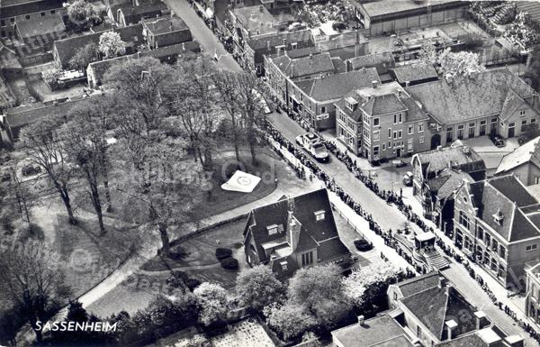 An0019-20 <br /> Luchtfoto van het centrum dorp (KLM Aerocarto). Midden onder villa 'Rusthoff'. Hoofdstraat loopt van linksboven (zuid) naar rechts-onder (noord). Uiterst rechtsonder het postkantoor. Het bloemencorso passeert. Foto: begin jaren '60.
