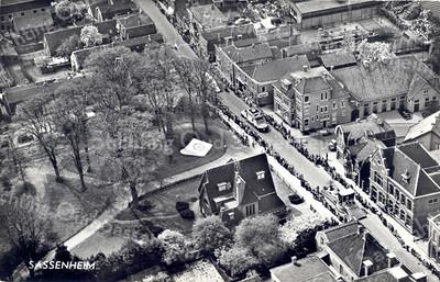 An0019 <br /> Luchtfoto van het centrum dorp (gemaakt door KLM Aerocarto). Midden onder villa Rusthoff met een mozaïek bij de ingang van het park. Hoofdstraat loopt van linksboven (zuid) naar rechtsonder (noord). Uiterst rechtsonder het postkantoor. Op de hoek van de Charbonlaan het KSA-gebouw. <br /> Het is de dag van het bloemencorso door het dorp rijdt. Foto: begin jaren '60.