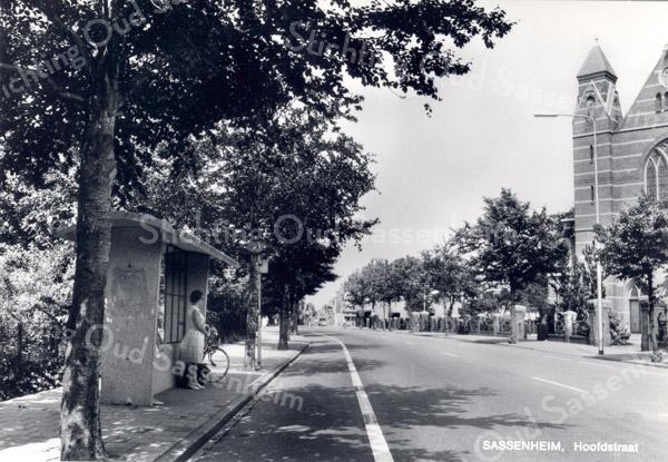 An0063 <br /> Gezicht op de Hoofdstraat in noordelijke richting. Rechts een gedeelte van de St. Pancratius. Links een bushalte. Foto: 1968