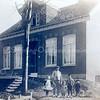 An0028 <br /> Vader Nico Breedijk met links Neeltje, rechts Kees, Klaas en Gep. In het tweede raam van rechts kijkt Nellie vanuit de kinderstoel toe. Breedijk was toen nog bollenkweker en had zijn land langs de Hoofdstraat. Later heeft hij de boerderij aan de Menneweg betrokken. De bijbehorende stal bestond uit voormalige huizen, die het 'Wespennest' genoemd werden. Het huis op de foto is huize Zonnehof aan de Hoofdstraat. Het huis is afgebroken in 1949, om de aanleg van de Parklaan mogelijk te maken.  Foto: ca. 1917.