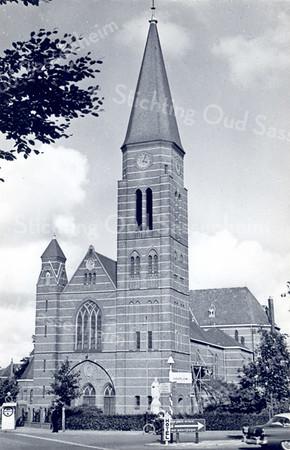An0010<br /> Vooraanzicht van de St. Pancratiuskerk na de grootscheepse nieuwbouw van 1913 tot 1929. De kerk is gebouwd door aannemer W. de Vrede uit Noordwijk, bouwsom f 149.300. De kerk werd op 2 oktober 1929 ingewijd. Aan de bouw is de naam van pastoor J.H.A. Thus voorgoed verbonden. Deze pastoor diende de parochie van 1911 tot 1932. Achter de wegwijzers is het beeld van 'Christus Koning' te zien. Foto: begin jaren '60.