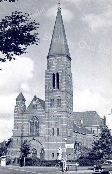 An0010<br /> RK-kerk St. Pancratius vooraanzicht na de grootscheepse nieuwbouw van 1913 tot 1929. De kerk is gebouwd door aannemer W. de Vrede uit Noordwijk, bouwsom f 149.300,-. De kerk werd op 2 oktober 1929 ingewijd. Aan de bouw is de naam van pastoor J.H.A. Thus voorgoed verbonden. Deze pastoor diende de parochie van 1911 tot 1932. Foto: begin jaren '60.