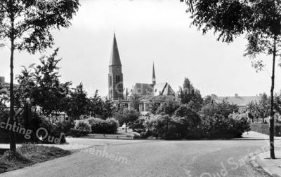 An0006 <br /> Foto vanaf de Menneweg. Links Dr. de Visserlaan, in het midden het plantsoen met de waterpartij en rechts tussen het geboomte door enkele huizen aan de St. Antoniuslaan. Achter de vijver zien we de Don Bosco-mulo en daar weer achter de St. Pancratiuskerk. Foto: begin jaren '60.