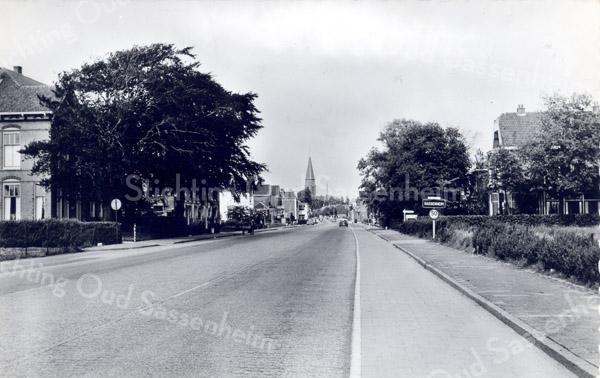 An0011<br /> Hoofdstraat, ongeveer ter hoogte van 'Twins Home' (links), kijkend in noordelijke richting. Rechts bord 'Sassenheim'. In de verte de toren van de RK-kerk St. Pancratius. Voor 'Twins Home' twee kolossale beukenbomen. Foto: begin jaren '60.