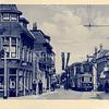 An0096 <br /> De kapperszaak van Jan de Jong, grenzend aan het kerkpad. Dit pand is in 1959 verdwenen. Midden op de prent de elektrische tram, die gereden heeft van 1933 tot 1949. Kaart heeft postaal gelopen, gefrankeerd met een postzegel van 2x 1,5 cent. Foto: ca 1933.