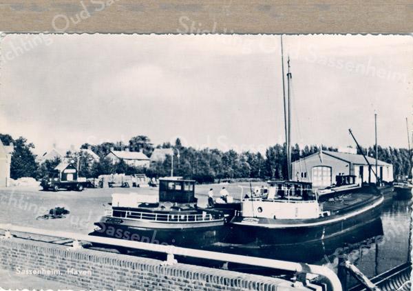 An0052 <br /> Op de voorgrond de brug van de Parklaan over de Oosthaven. Links een schuit van rederij B. de Boer en rechts een schuit uit Bodegraven. Op de achtergrond de opslagloods van rederij Wesseling. Uiterst links het gebouw van Openbare Werken en de huizen langs de Willem Warnaarlaan. Zie ook 'Sassenheim in Grootmoeders tijd', blz 29. Kaart heeft postaal gelopen en is gefrankeerd met postzegel van 4 cent. Foto: jaren '50.
