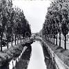 An0007<br /> De Zandsloot gezien vanaf de Oude Postbrug in westelijke richting. Links de Postwijkkade en rechts de Zandslootkade, omzoomd met bomen. Op de Postwijkkade een vrachtauto. Foto: begin jaren '60.