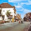 An0038 <br /> Hoofdstraat, gezien in noordelijke richting. Links hotel café-restaurant 'Het Bruine Paard'. Op de achtergrond het torentje van sigarenmagazijn van Barend van Loo. Rechts de ingang van de Kerklaan met de stoffenzaak van De Haas en de winkel van Expert. Verderop nog de snoepwinkel van Jamin. Foto: 1974.
