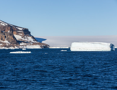 Tabular iceberg (foreground) and glacier on the Tabarin Peninsula west of Joinville Island. 3:30 AM. Antarctica.