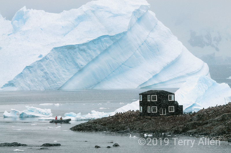 Tilted-iceberg-&-zodiac-in-snow-storm,-Almirante-Brown,-Antarctic-Penninsula