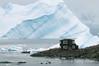 Tilted-iceberg-&-zodiac-in-snow-storm,-Almirante-Brown,-Antarctic-Penninsula