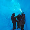 Inside the ice cave on Erebus Ice Tongue. The ice caves are snow-covered crevases at the snout of the Erebus Ice Tongue. The ice filters the natural sunlight and illuminates the caves with a beautiful diffuse blue light. Stalactite-like icicles on the cave ceilings and huge ice crystals formed by sublimation add to the natural beauty of this amazing place.