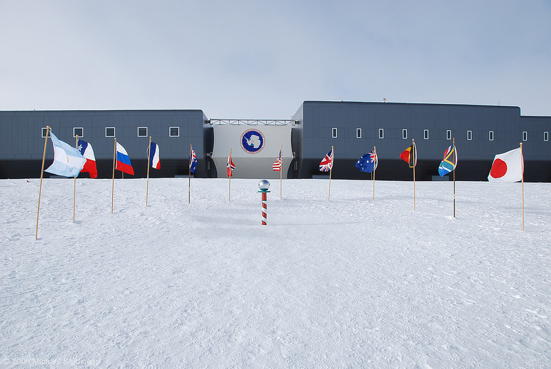 The ceremonial South Pole with the new Amundsen-Scott South Pole Station in the back.