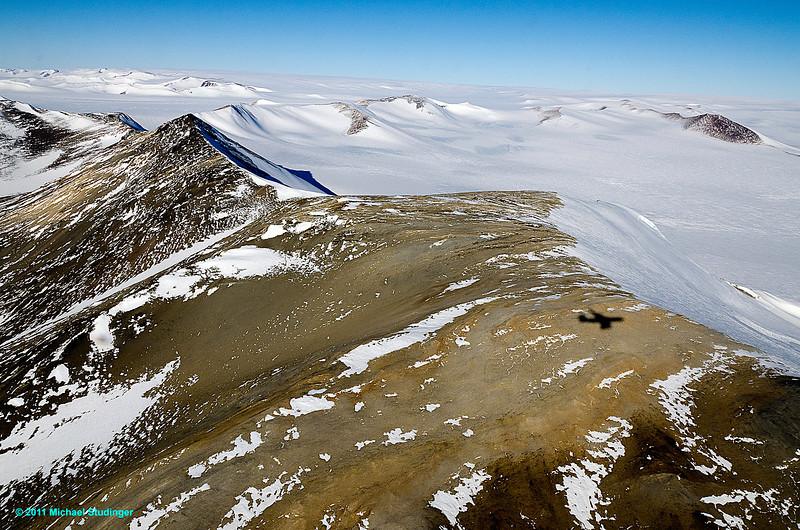 The shadow of the DC-8 can be seen below the aircraft while flying over a ridge in the Shackleton Range in Coats Land, East Antarctica.