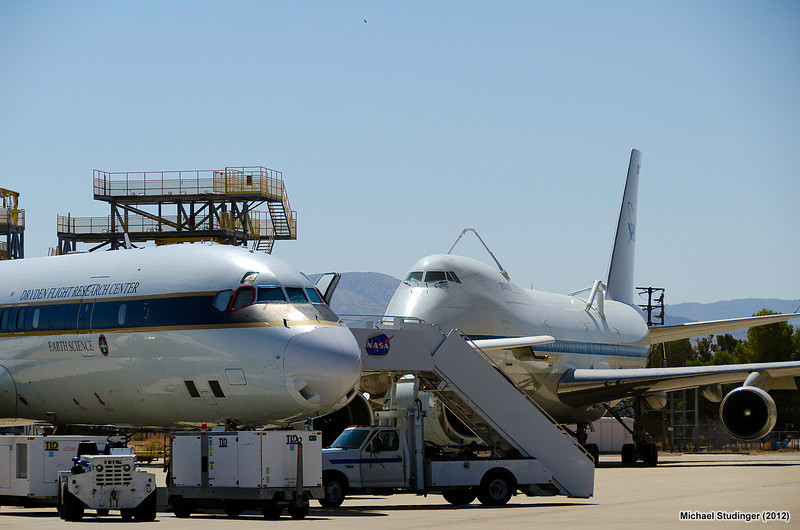 NASA's DC-8 research aircraft is being prepared for an IceBridge test flight over targets in the Mojave Desert. In the background is one of the two Shuttle Carrier Aircraft; a modified Boing 747 airliner; that was used to transport the Space Shuttle orbiters from landing sites back to the Kennedy Space Center. The two Schuttle Carrier Aircraft were retired in 2012.